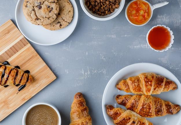 Croissants in een bord met koffie, bonen, koekjes, jam, honing plat lag
