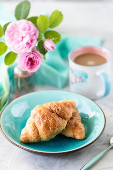 Croissants in een mooi bord met een boeket roze rozen.