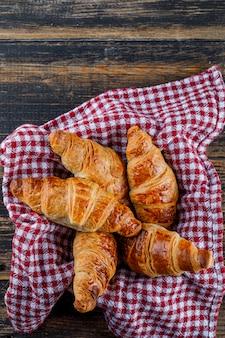 Croissants in een pan met handdoek op een houten tafel. plat lag.