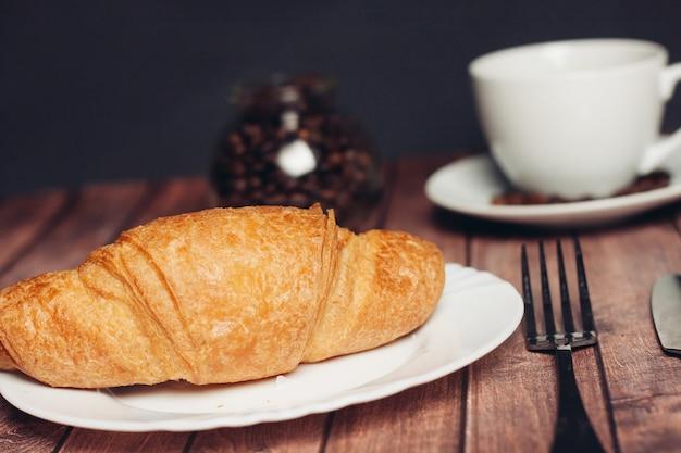 Croissants in een plaat op de koffiemaaltijd van het lijstdessert