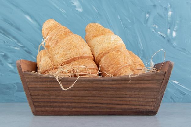 Croissants in houten kom op de marmeren achtergrond. hoge kwaliteit foto