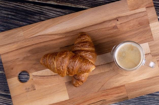 Croissants met een kopje koffie op een houten bord.