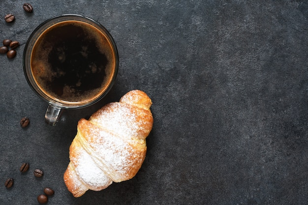 Croissants met espresso op een zwarte betonnen ondergrond. uitzicht van boven.