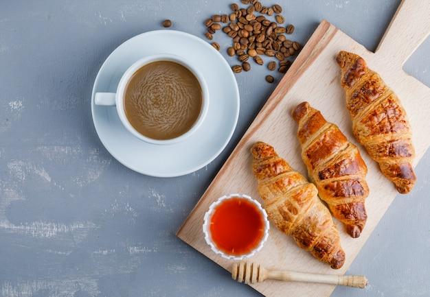 Croissants met koffie en bonen, honing, beer op gips en snijplank, plat lag.