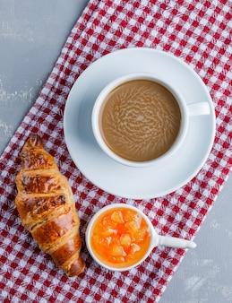 Croissants met koffie, saus op gips en picknickdoek, plat liggen.