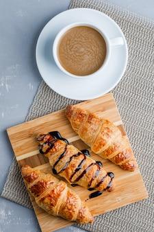 Croissants met koffie, snijplank, plat lag.