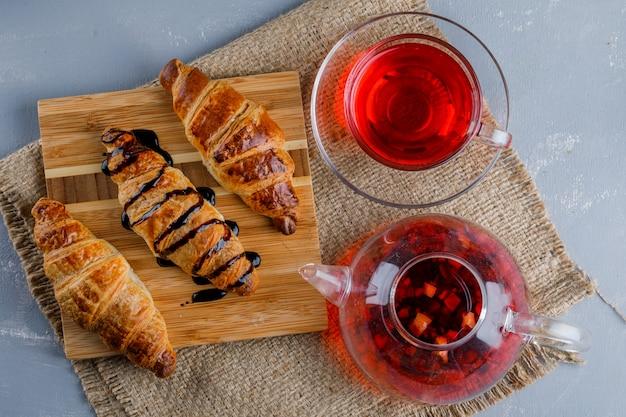 Croissants met saus, thee, houten plank op gips en stuk zak, plat leggen.