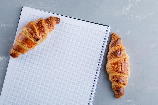 Croissants met spiraal notitieboekje, plat.