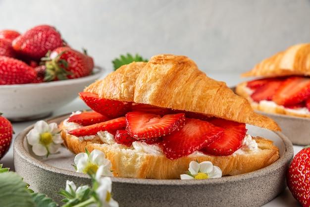 Croissants met verse aardbeien en roomkaas in een bord met bloemen voor een smakelijk ontbijt