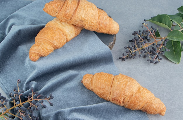 Croissants op een handdoek met druiven op de marmeren vloer, op de marmeren achtergrond. hoge kwaliteit foto