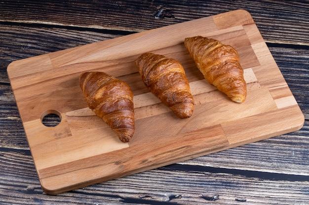 Croissants op een houten bord.