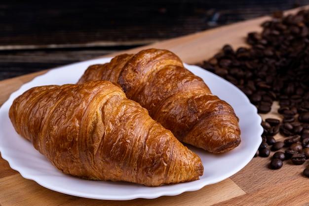 Croissants op een witte plaat en koffiebonen op een houten bord