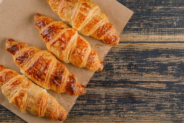 Croissants op houten en papieren zak. plat lag.