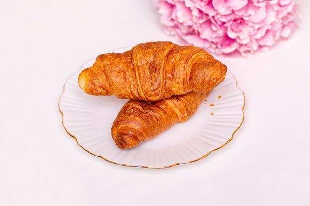 Croissants op plaat met hortensia bloem op witte achtergrond