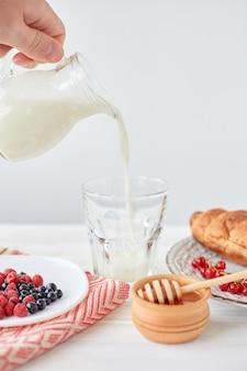 Croissants op plaat op het houten bord, bessen, koffie, melk en honing op een wit tafellaken. mannenhand giet melk in een glas met koffie. lifestyle. kopieer ruimte