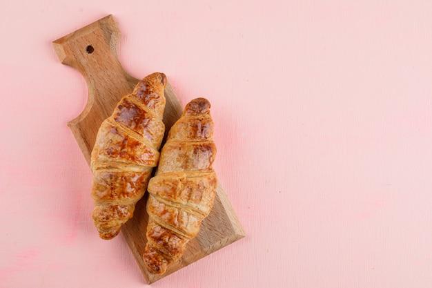 Croissants op roze en snijplank, plat lag.