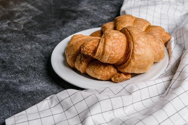 Croissants op witte ronde plaat en grijze tafelmuur