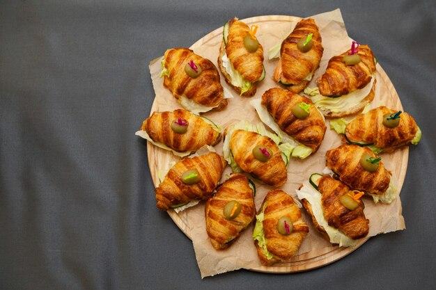 Croissants sandwiches met vis op een ronde houten plank.