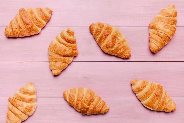 Croissants verspreid op roze tafel