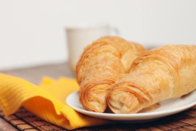 Croissants witte platen op tafel keukengerei een kopje. hoge kwaliteit foto