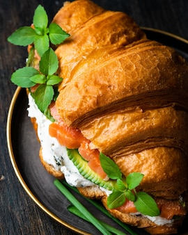 Croissantsandwich met gezouten zalm op zwarte plaat, geserveerd met verse basilicumbladeren, avocado en philadelphia-kaas. frans ontbijt. gezond eetconcept.