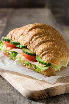 Croissantsandwich met kaas, ham en groenten op houten lijst
