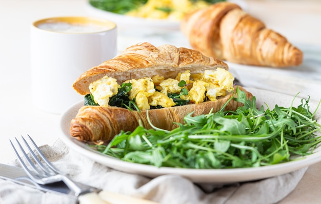Croissantsandwich met roerei spinazie-eieren geserveerd met rucola op plaat en koffiekopje.