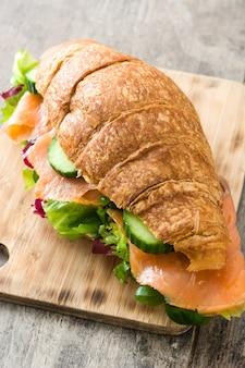 Croissantsandwich met zalm en groenten op houten lijst