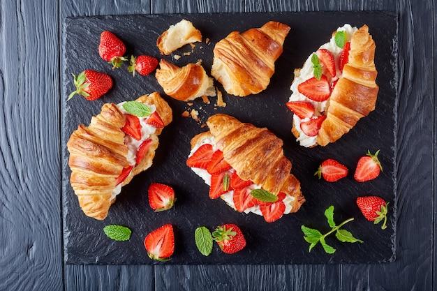 Croissantsandwiches gelaagd met verse rijpe aardbeien en slagroomkaas op een stenen dienblad op een zwarte houten tafel