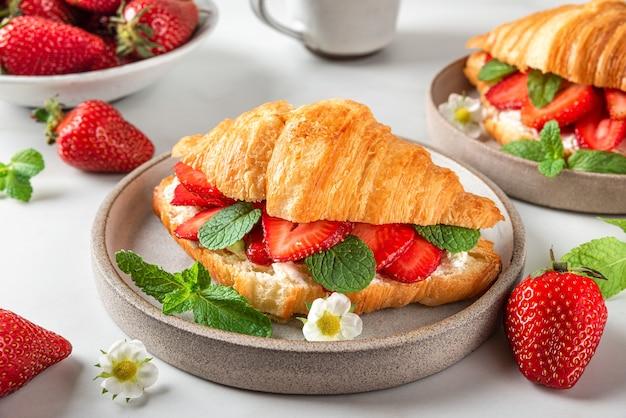 Croissantsandwiches met verse rijpe aardbeien en roomkaas in een bord met kop koffie voor smakelijk ontbijt op witte tafel
