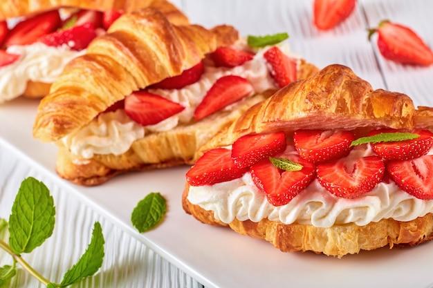 Croissantsandwiches met verse rijpe aardbeien en slagroomkaas op een schotel op witte houten lijst