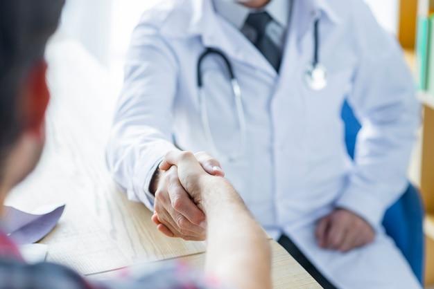 Crop arts en patiënt schudden handen op kantoor