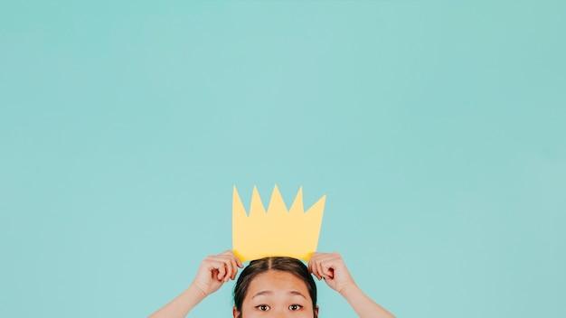 Crop aziatische vrouw met papieren kroon