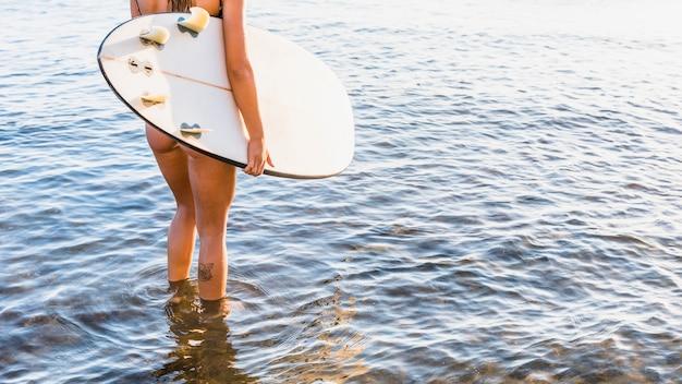 Crop dame met surfplank in zee