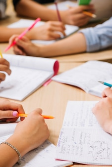 Crop handen van studenten op bureaublad