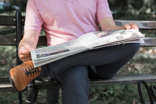 Crop man leest de krant op de bank