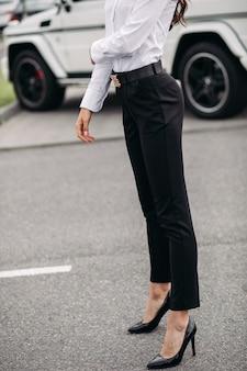 Croppe foto van modieuze en stijlvolle dame gekleed in zwarte broek en witte blouse poseren op de achtergrond van een auto buitenshuis