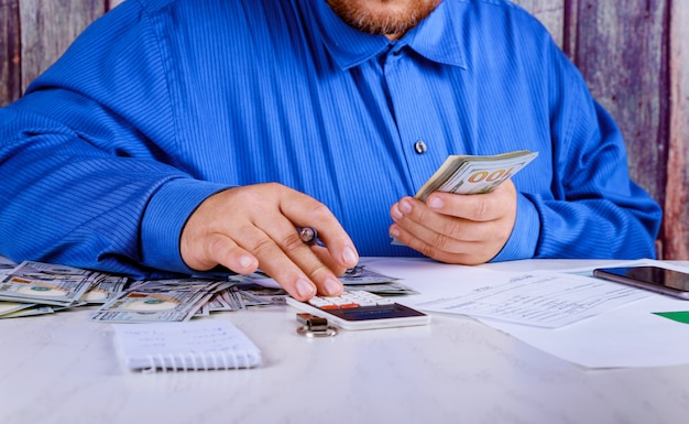 Cropped boekhouder met behulp van calculator geld tellen