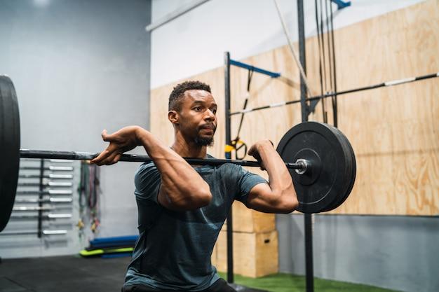 Crossfit-atleet die oefening doet met een barbell.
