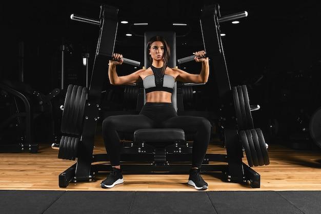 Crossfit-concept, meisje op simulator met grote gewichten