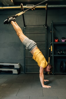 Crossfit fitness trx push ups man training bij sportschool. kracht en concentratie. jonge knappe man in sportkleding uitoefenen op sportschool.