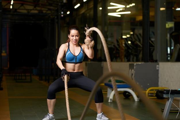 Crossfit-oefening uitgevoerd door een sterke vrouw met touw