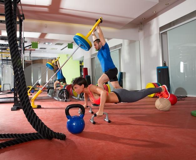 Crossfit vrouw push ups oefenen en man gewicht tillen