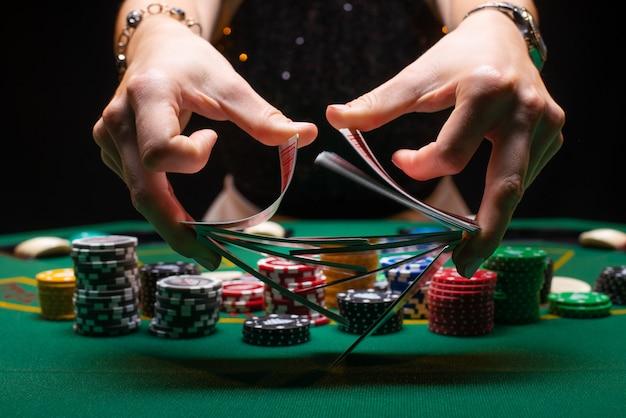 Croupier van het meisje schuifelt pokerkaarten in een casino