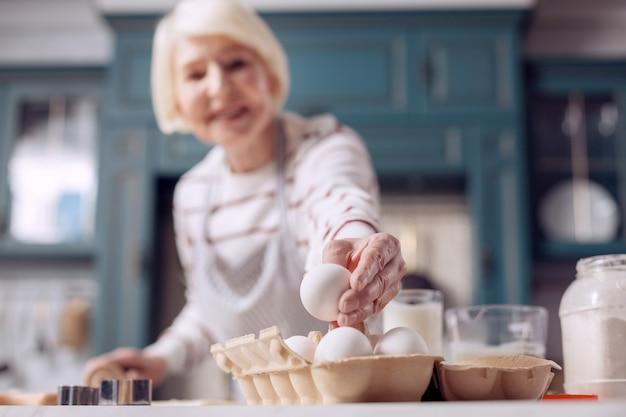 Cruciaal ingrediënt. de focus ligt op de hand van een charmante oudere dame die een ei uit een eierdoos haalt en glimlacht terwijl ze deeg voor een taart maakt