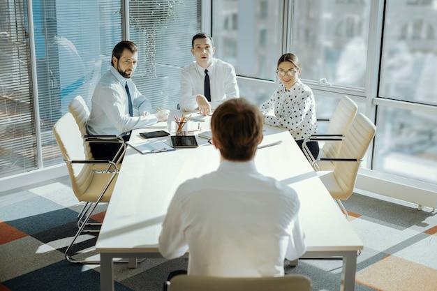 Cruciale ontmoeting. het achteraanzicht van een jonge mannelijke ceo die aan het hoofd van de tafel zit en een vergadering houdt met zijn managers, waarbij hij afstand houdt tussen hem en hen