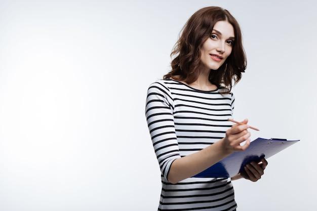 Cruciale opmerkingen. mooie kastanjebruine jonge vrouw die op een blad schrijft dat aan een houder is vastgemaakt terwijl ze op grijs glimlacht