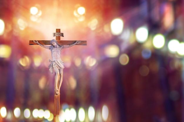 Crucifix, jezus aan het kruis in de kerk met lichtstraal van gebrandschilderd glas, paasfeest van de christelijke kerk