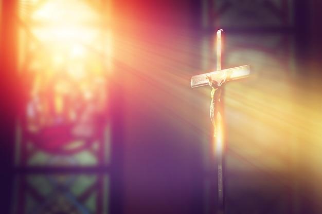 Crucifix, jezus op het kruis in de kerk met lichtstraal van gekleurd glas