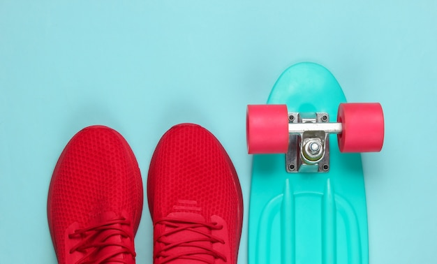 Cruiser board en rode sneakers op blauwe achtergrond.